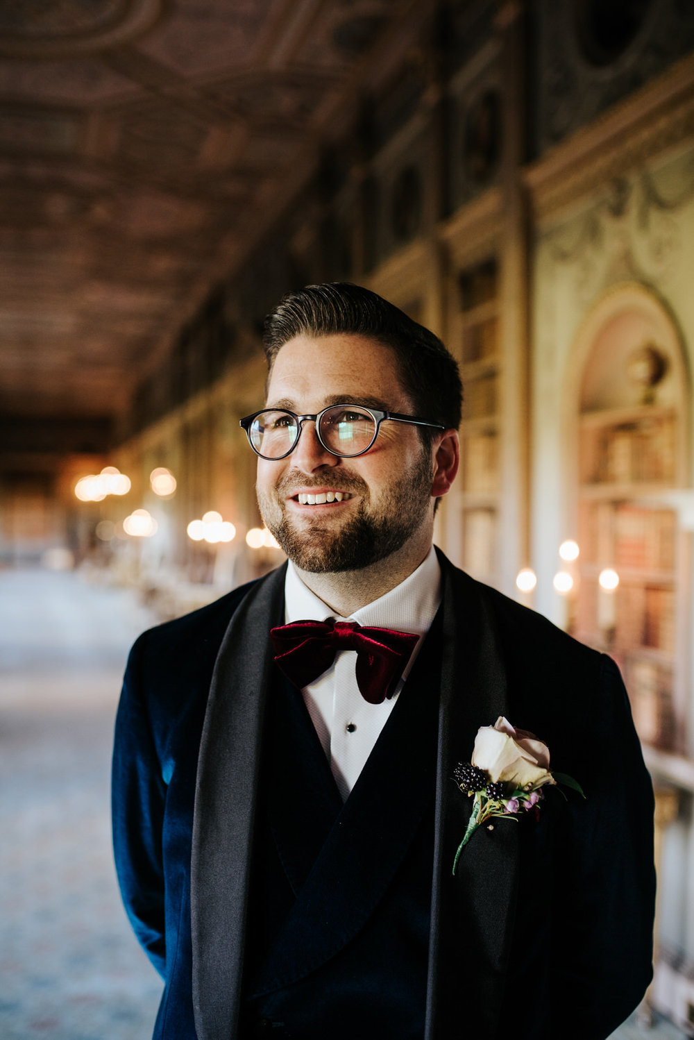 Candid portrait of the groom as he stands in Syon House's library room and looks dapper