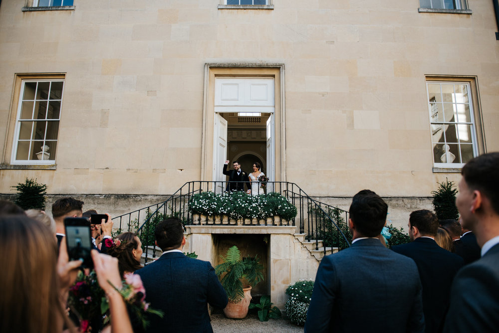 Bride and groom are announced into Syon House inner courtyard as their guests smile and applaud