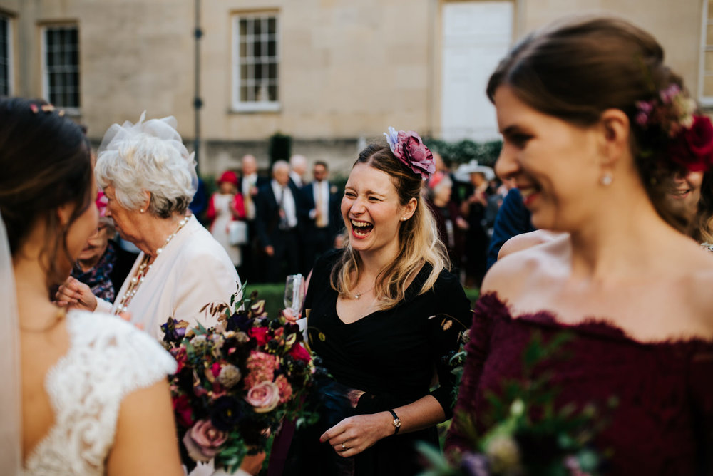 Candid moment of guests saying hello to bride and groom after wedding ceremony
