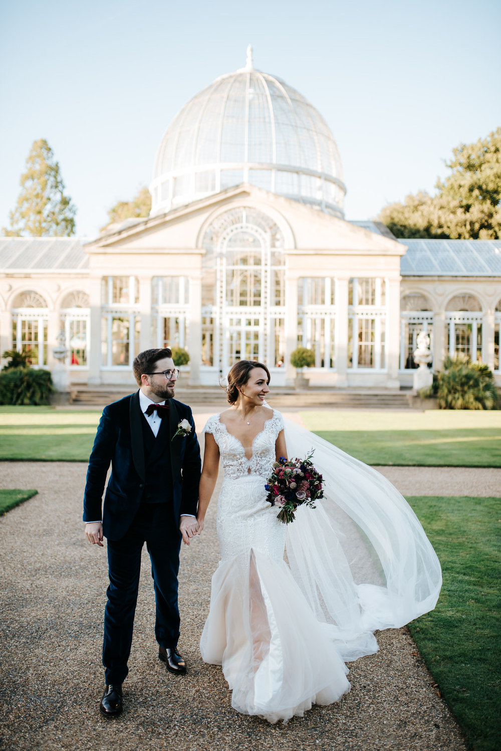Bride and groom walk towards camera as great conservatory building towers from behind them