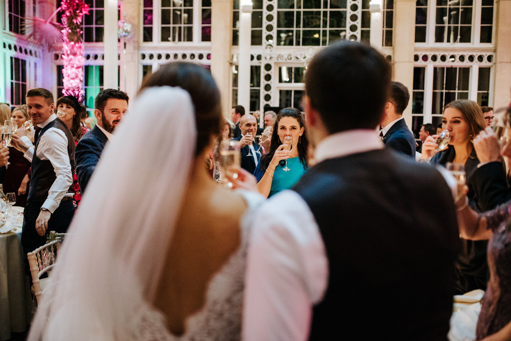 Bride and groom stand centre, out of focus, as guests toast behind them