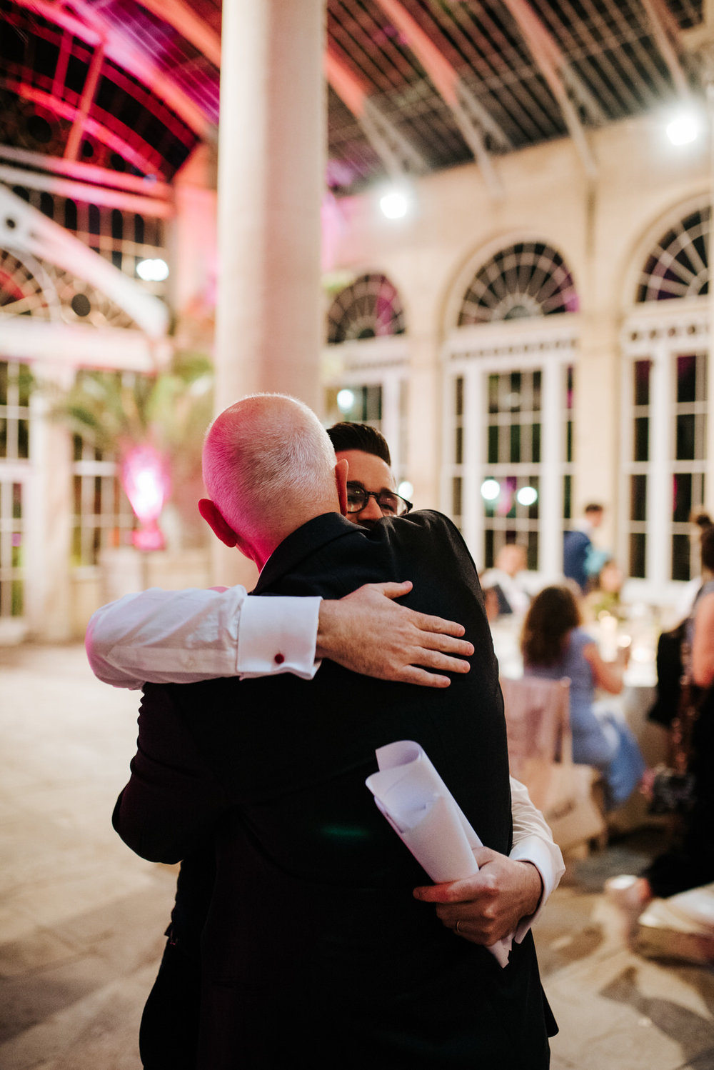 Groom tightly hugs his dad after he finishes his wedding speech