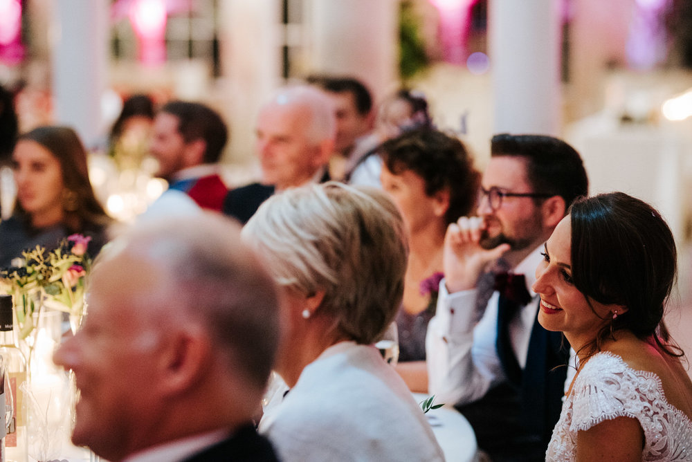 Bride and groom smile as they listen to groomsmen deliver emotional speech