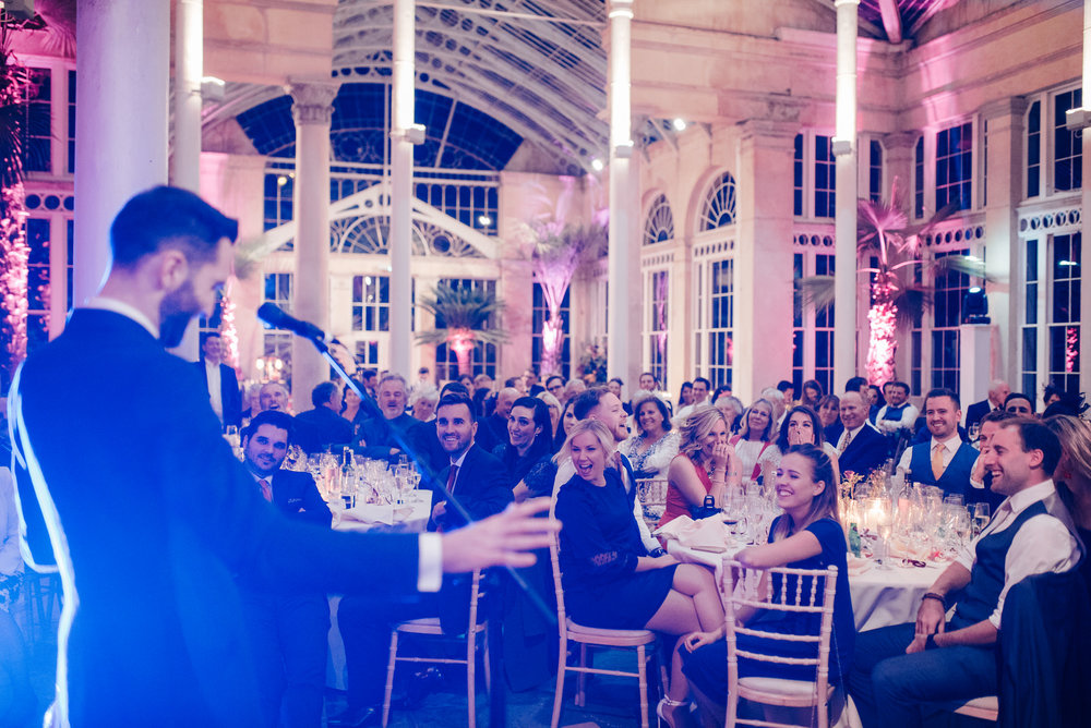 Groomsman delivers his speech while the audience is in tears of laughter