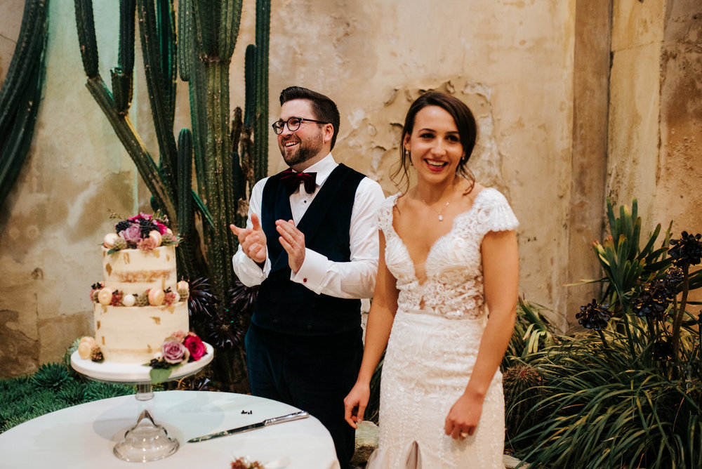 Bride and groom stand and smile moments before cutting their wedding cake