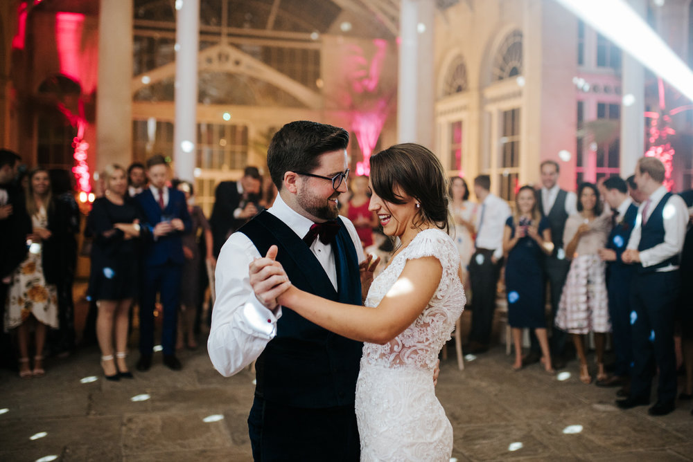 Bride and groom hold hands and dance during first dance as guests look from the back