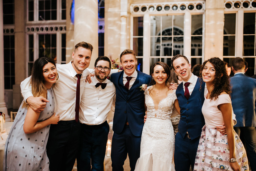 Group photo of bride, groom and guests looking at camera