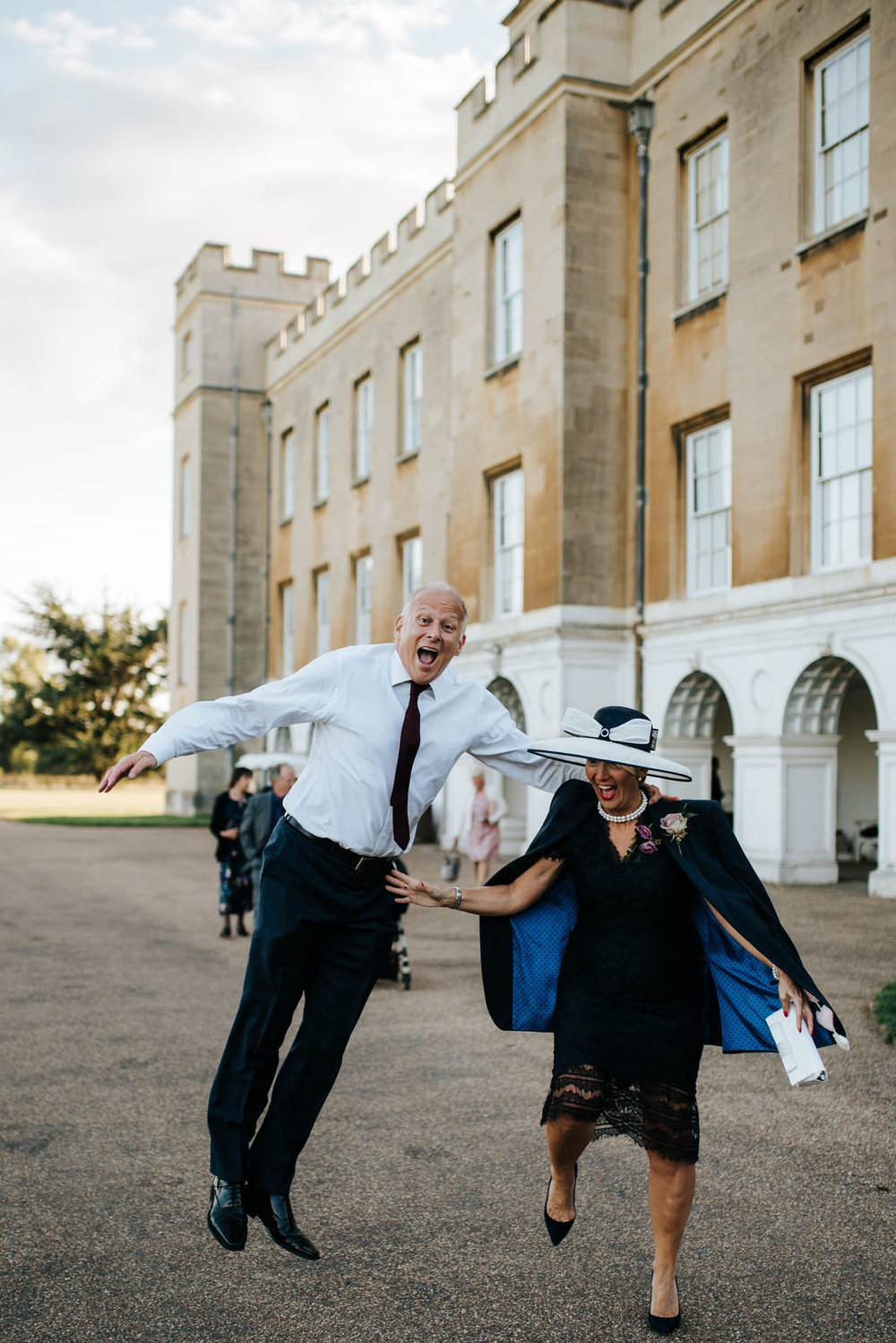 Bride's step-dad and mum jump with joy as they walk towards Syon Park Grand Conservatory