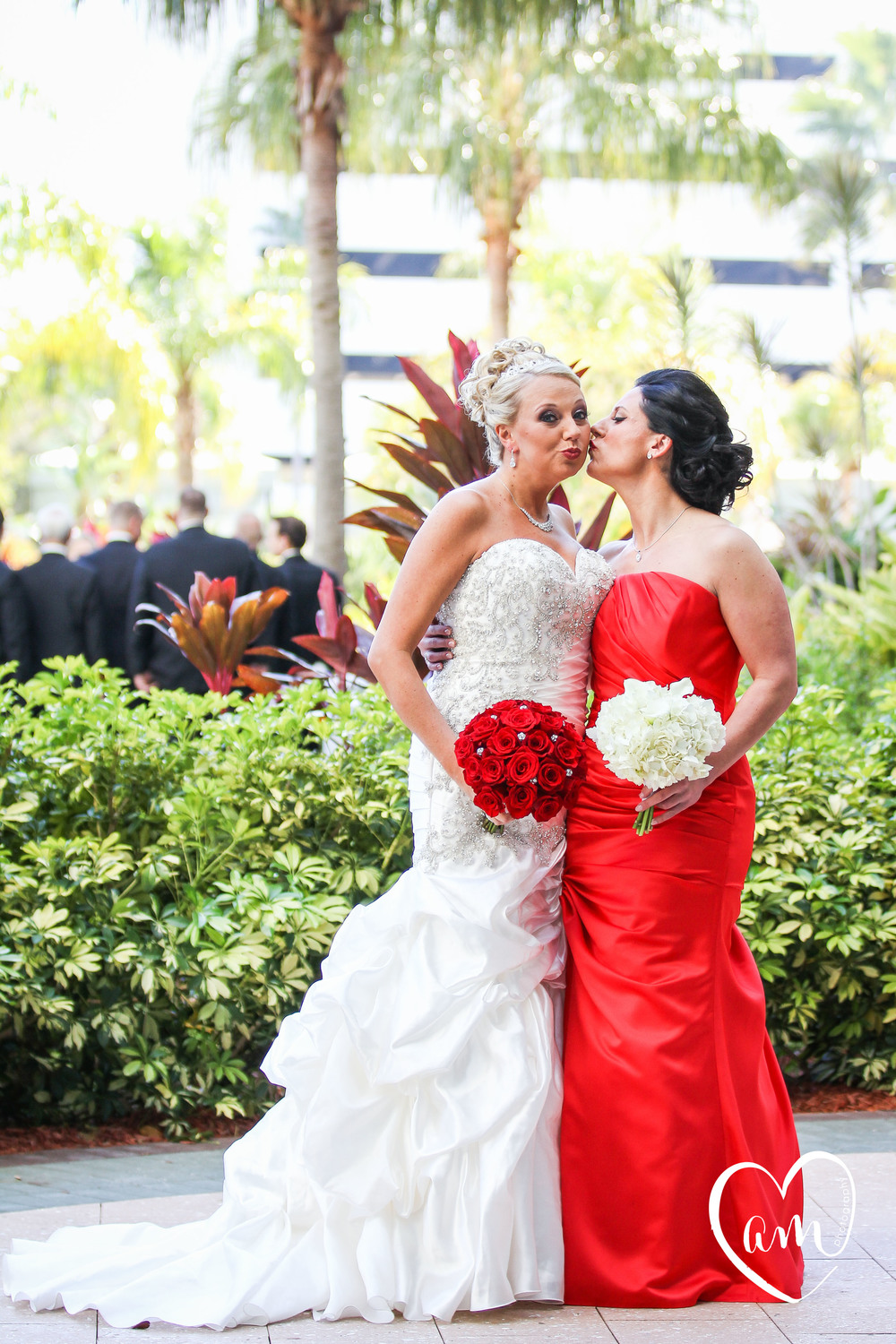 bride and bridesmaid take silly wedding formal photo