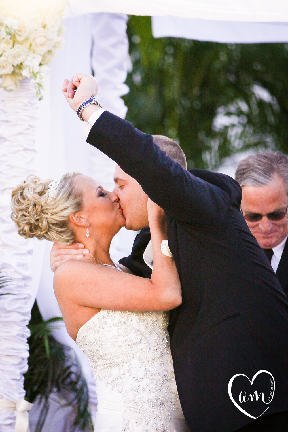 groom fist pumps during first kiss with new wife in joyful orlando wedding ceremony