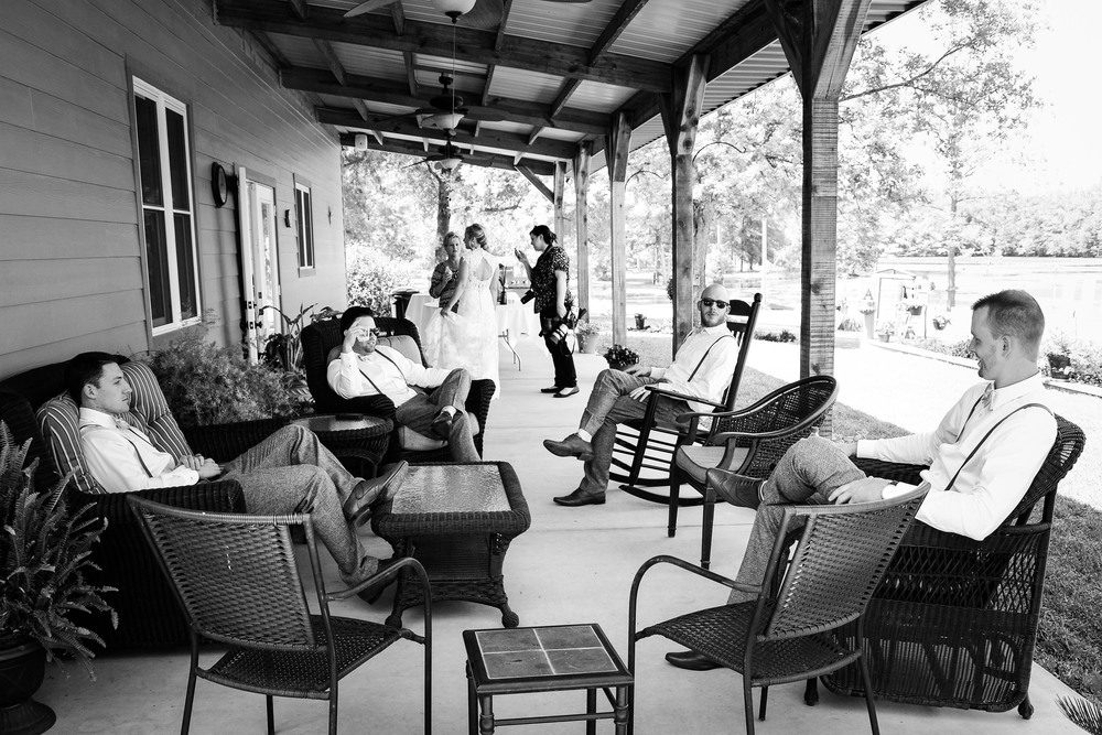 The groomsmen taking some shelter from the sweltering sun and hanging out in the shade.