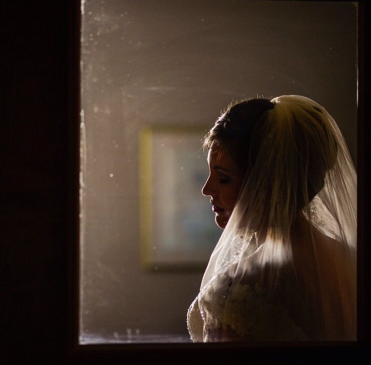 Creation:  A bride photographed through a door on her wedding day.
