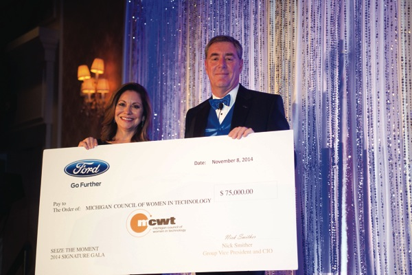 Nick Smithers presents Maru Flores, MCWT president, with a $75,000 grant from Ford Motor Company for leasing office space in Dearborn