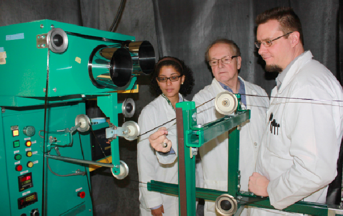 MSU professor Lawrence Drzal (center) discusses the operation and advantages of an ultraviolet light-ozone carbon fiber treatment line with Mariana Batista of Bahia, Brazil, and Markus Downey of Narragasett, R.I. Batista is a doctoral student in materials science and Downey is a doctoral student in chemical engineering. MSU developed and patented this process, which uses ozone and high-intensity ultraviolet light to improve the adhesion of composite materials.  Photo by Patricia Mrocze