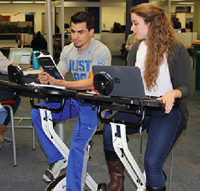 Oakland University students try out the school's new FitDesks.