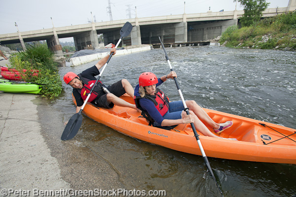 A couple launches their kayak from the banks of the LA River along the Glendale Narrows section, a soft-bottomed section of the river.