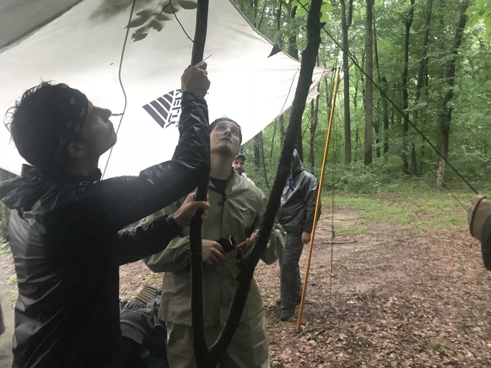 Levi and other participants from 2018's Executive Summit Wilderness Excursion crafting a rain shelter.