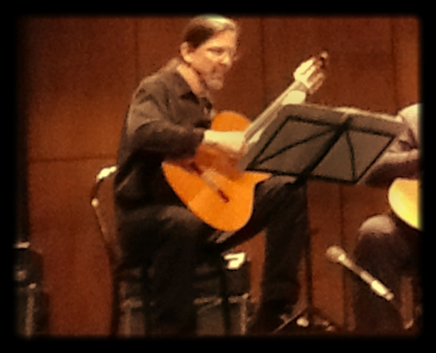 John playing classical guitar at a college concert