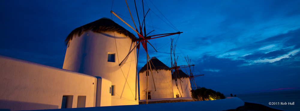A wide angle lens captures the windmills and the twilight sky in Mykonos, Greece.
