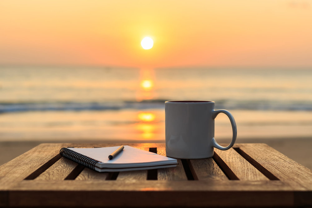 47639945 - close up coffee cup on wood table at sunset or sunrise beach
