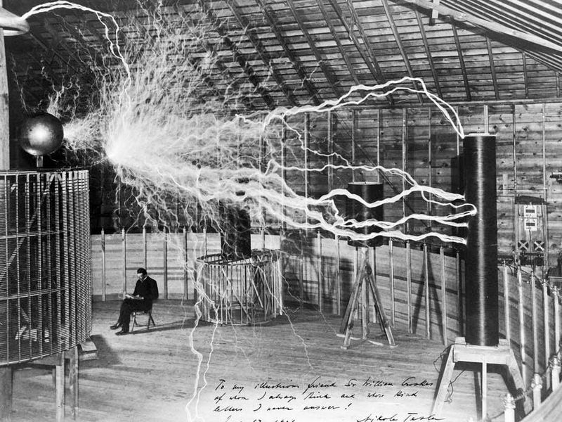 """Publicity photo of Nikola Tesla in his laboratory in Colorado Springs, Colorado, in December 1899. Tesla posed with his """"magnifying transmitter,"""" which was capable of producing millions of volts of electricity. The discharge shown is 6.7 meters (22 feet) in length."""