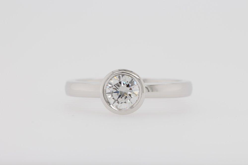 Bezel set round diamond engagement ring.