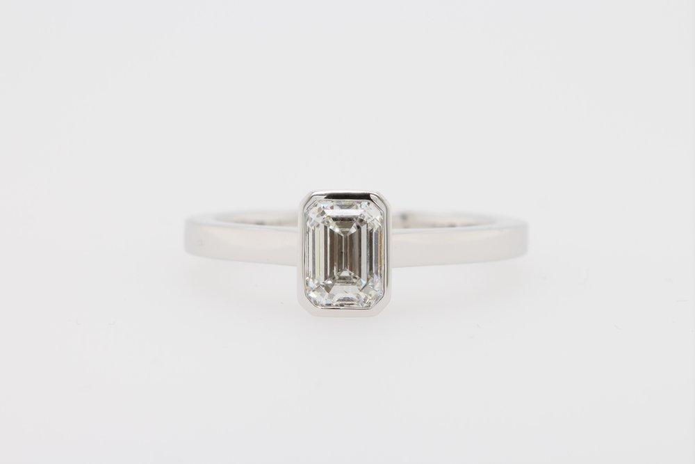 Bezel set emerald cut diamond engagement ring.