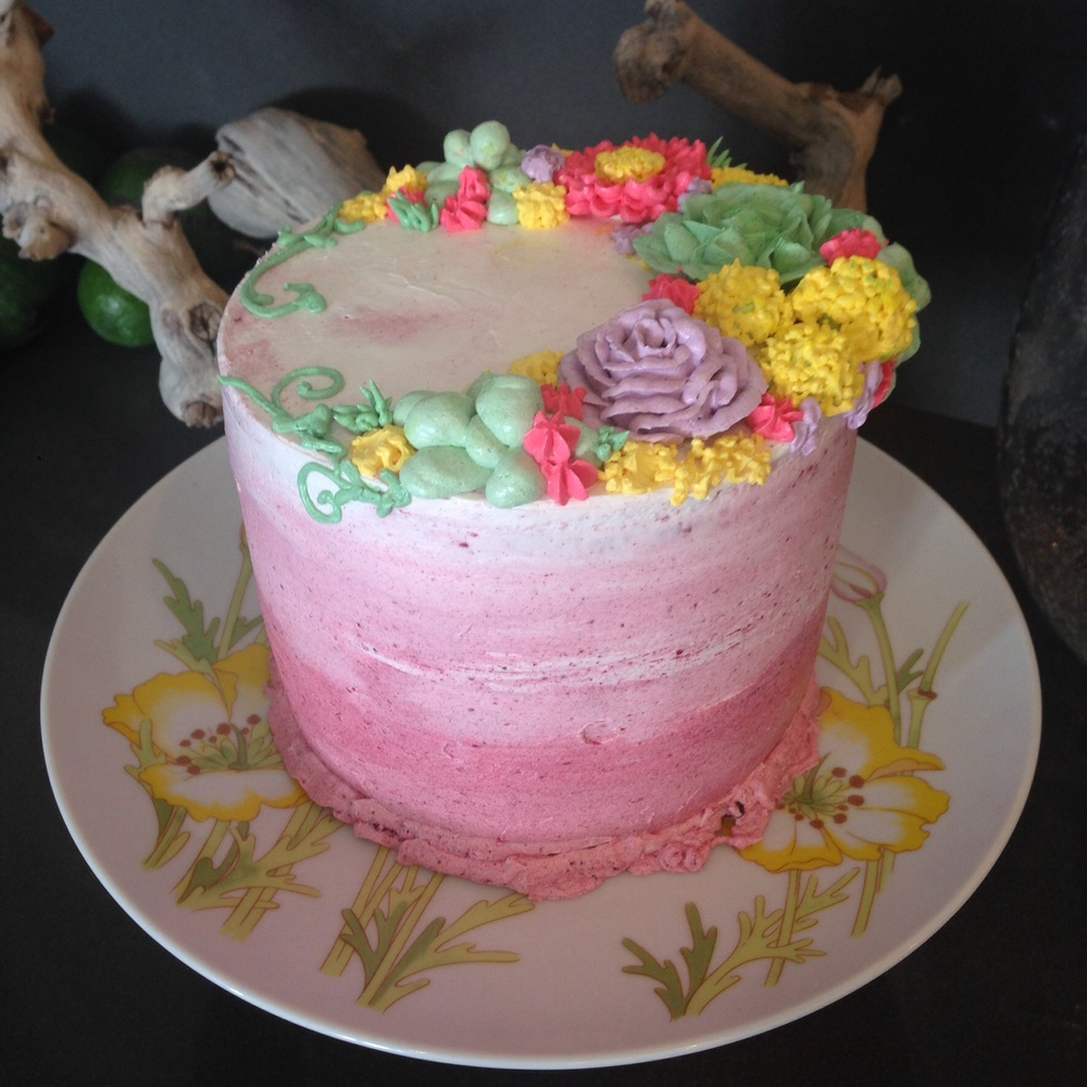Ground up freeze dried raspberries in buttercream created this ombré pink beauty. It was also ombré pink inside. Buttercream flowers and succulents made this sweet little birthday cake a real stunner.