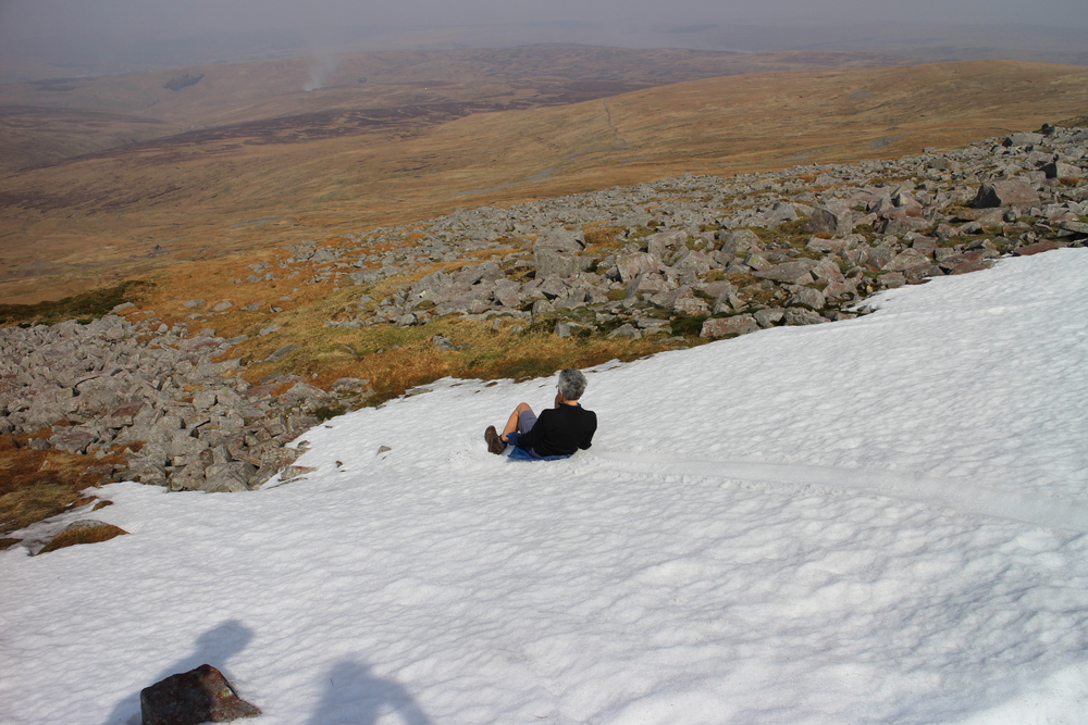 Sue sledding down from Cross Fell