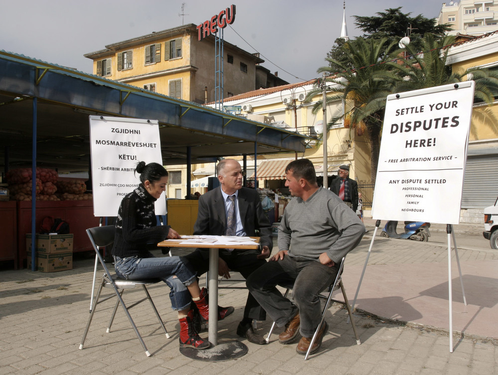 Conflict Management   ,   Carey Young   2003 -   Professional arbitrator, table, chairs, two noticeboards, media advertising, members of the public.   Commissioned by Museum Ludwig, Budapest