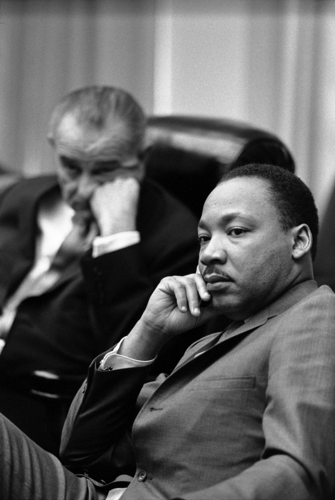 Dr. Martin Luther King in the White House with LBJ in the background.