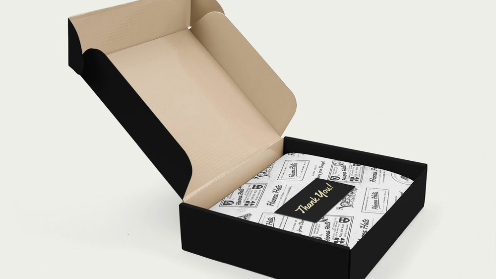 With the black box design, we would incorporate a white tissue wrapping featuring all the historical logos which again lends a tasteful, premium impression and it's matched with a black sticker with golden typography
