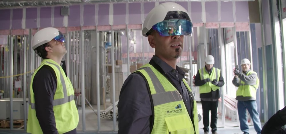 "Construction workers wearing Daqri headsets so that they can ""see"" where ducting, electrical, plumbing, and other systems are to be located based on architectural plans."