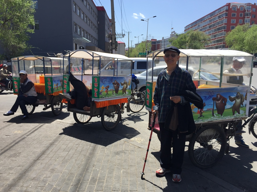 The older Dr. Liu in front of some rickshaws.