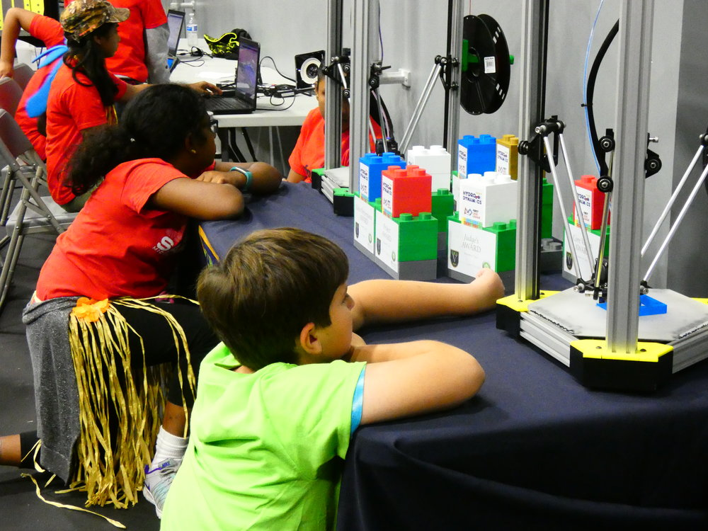 Students watch 3D printers create imitation LEGO Bricks. The trophies for the event, used to recognize teams with the strongest performance and achievement of the  FIRST  LEGO League Objectives, were also composed of 3D-printed bricks. Photo by Kim Walters.