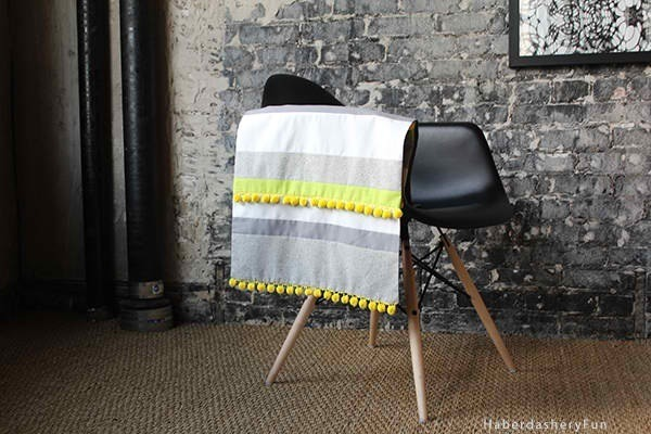 "Pom Poms Aren't Just For Cheerleaders!    Inspired by blogs Haberdashery Fun & Scissors & Thread - this image and Pom Pom Table Runner says- ""I ain't Afraid!""    We love Pom Poms - they add that bit of whimsy to any fabric or existing runner or tablecloth or just about anything you want to hot glue, stitch, or tape them to! ( lamp shades are great sources of DIY innovation as well).     The best part about this is that in minutes you have a fun styley and unique accessory!  So smile this weekend & DO NOT FEAR THE POM POM!"