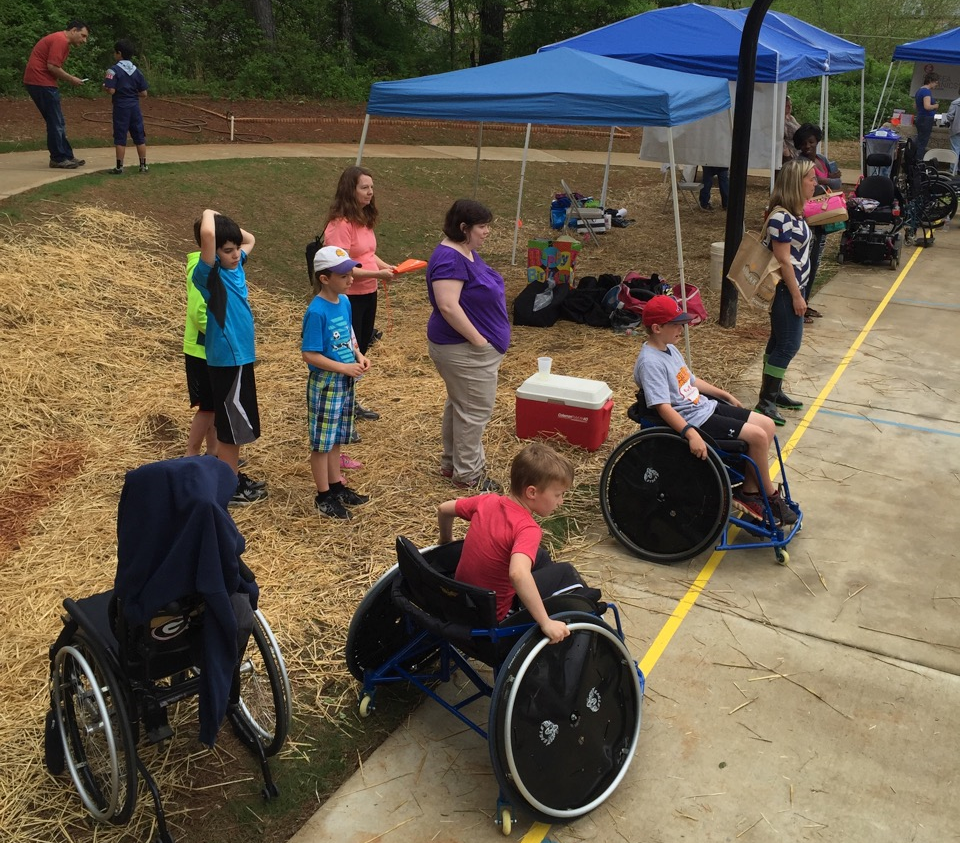 Lines of citizens form at the Milton Earth Day celebration waiting to learn wheelchair sports fundamentals from the Titans