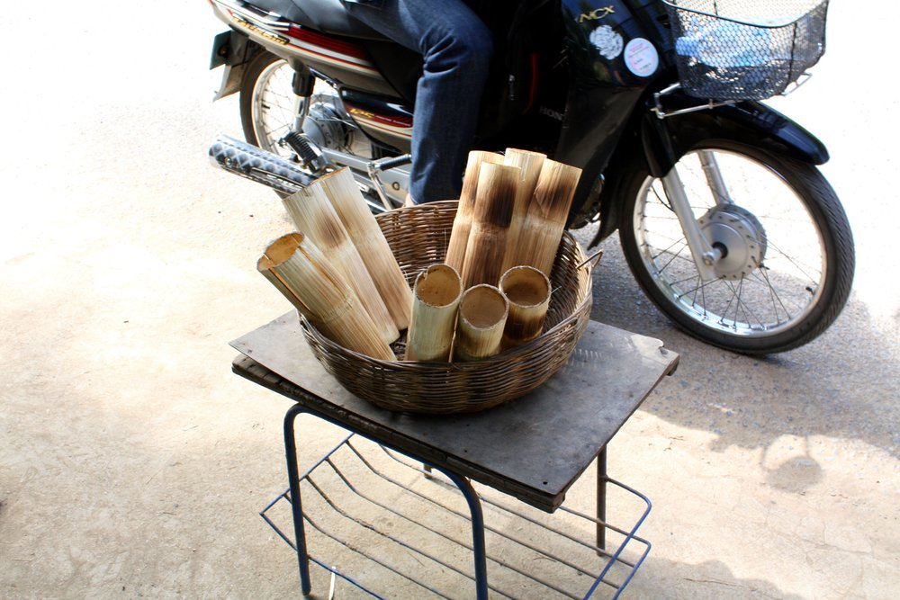 Bamboo sticky rice sold on the side of the road.
