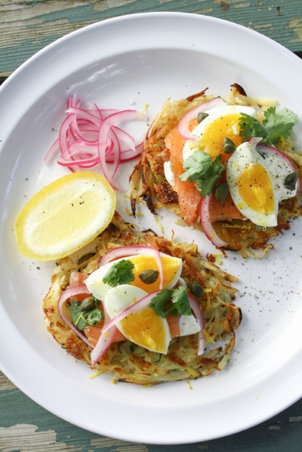 plate of smoked salmon served on rosti with pickled red onions cilantro and soft boiled eggs