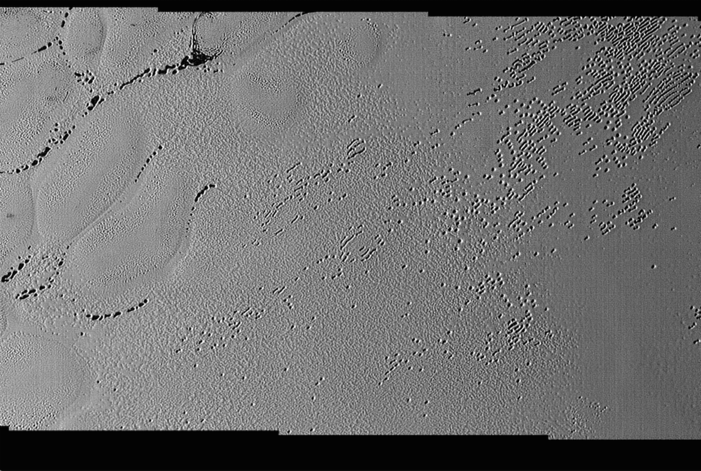 This image was taken by the Long Range Reconnaissance Imager (LORRI) on NASA's New Horizons spacecraft shortly before closest approach to Pluto on July 14, 2015; it resolves details as small as 270 yards (250 meters). The scene shown is about 130 miles (210 kilometers) across. The sun illuminates the scene from the left, and north is to the upper left. - Credits: NASA/JHUAPL/SwRI