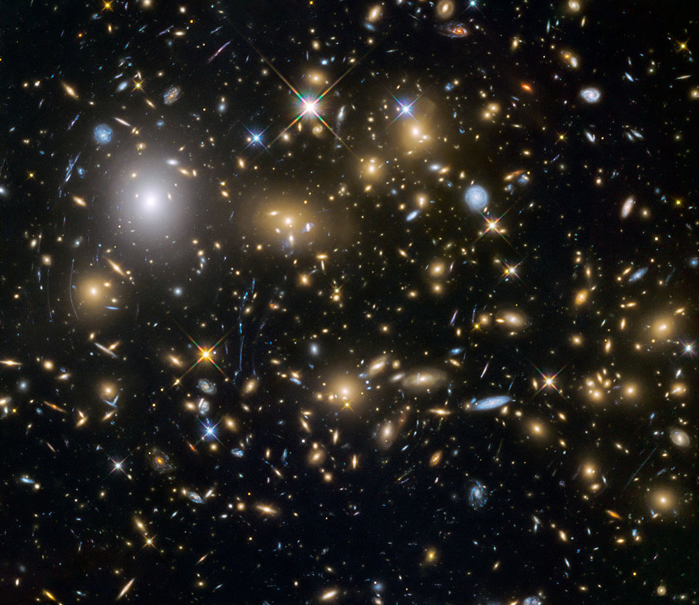 This image from the NASA/ESA Hubble Space Telescope shows the galaxy cluster MACSJ0717.5+3745. This is one of six being studied by the Hubble Frontier Fields programme, which together have produced the deepest images of gravitational lensing ever made. Due to the huge mass of the cluster it is bending the light of background objects, acting as a magnifying lens. It is one of the most massive galaxy clusters known, and it is also the largest known gravitational lens. Of all of the galaxy clusters known and measured, MACS J0717 lenses the largest area of the sky. - Credit: NASA, ESA and the HST Frontier Fields team (STScI)