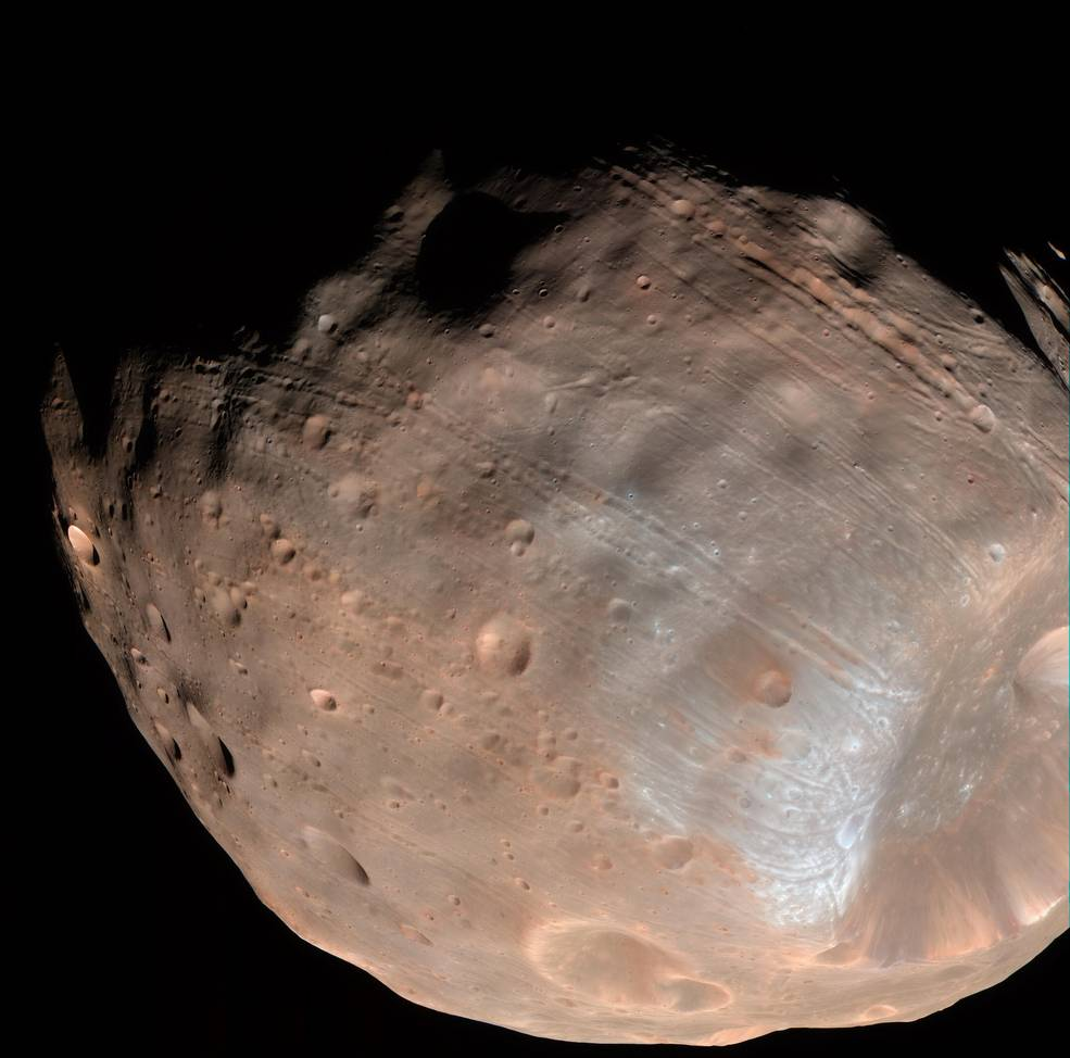 New modeling indicates that the grooves on Mars' moon Phobos could be produced by tidal forces – the mutual gravitational pull of the planet and the moon. Initially, scientists had thought the grooves were created by the massive impact that made Stickney crater (lower right). - Image credit: NASA/JPL-Caltech/University of Arizona