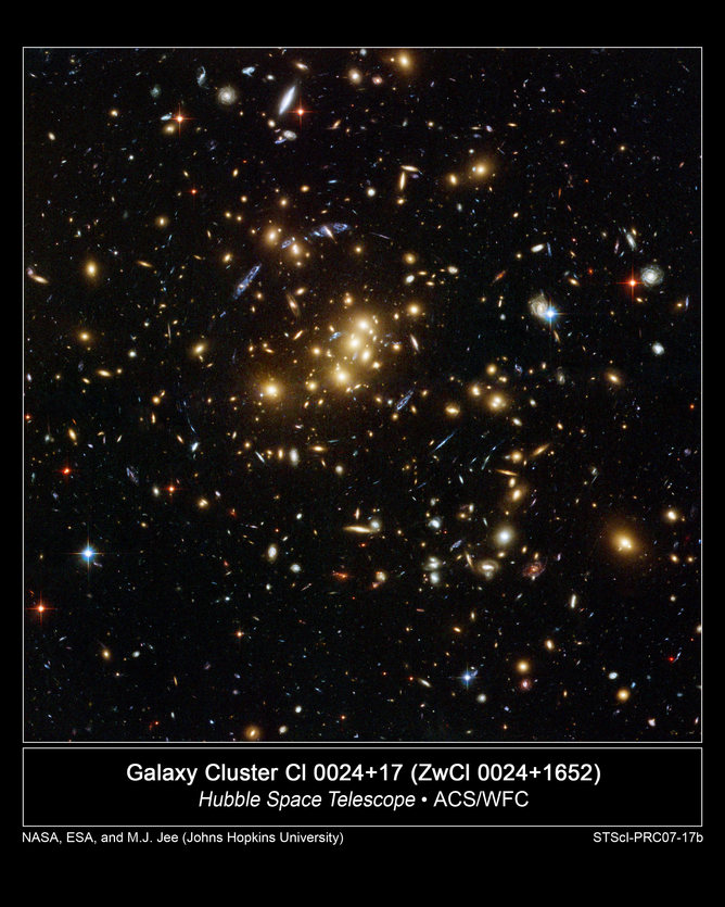 The rich galaxy cluster Cl 0024+17. Blue streaks near the centre are smeared images of very distant background galaxies. Their light is being bent and magnified by the intervening cluster, in an effect called gravitational lensing.