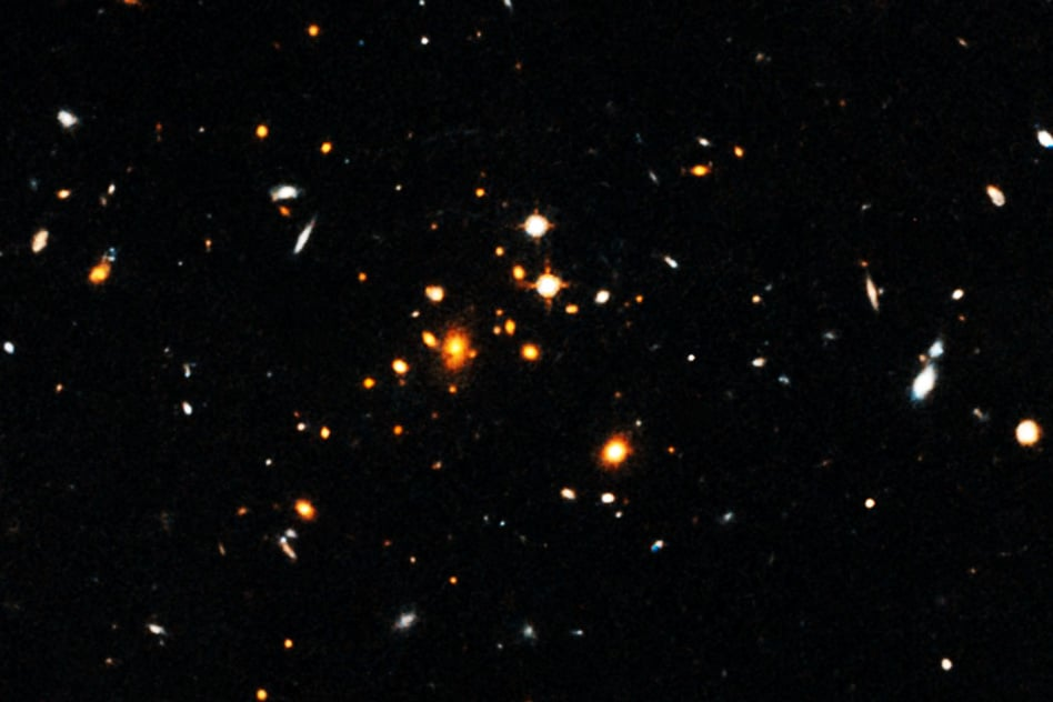 Astronomers have detected a massive, sprawling, churning galaxy cluster that formed only 3.8 billion years after the Big Bang. The cluster, shown here, is the most massive cluster of galaxies yet discovered in the first 4 billion years after the Big Bang. - Image Credit: NASA, European Space Agency, University of Florida, University of Missouri, and University of California