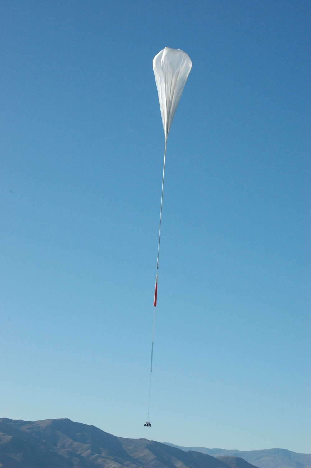 A NASA Super Pressure Balloon takes flight from Wanaka, New Zealand, in 2015. When fully inflated, the 18.8 million-cubic-foot (532,000 cubic meter) balloon is as large as a football stadium. During this year's New Zealand campaign, the balloon will carry the University of California, Berkeley's Compton Spectrometer and Imager (COSI) payload. - Image   Credits: NASA