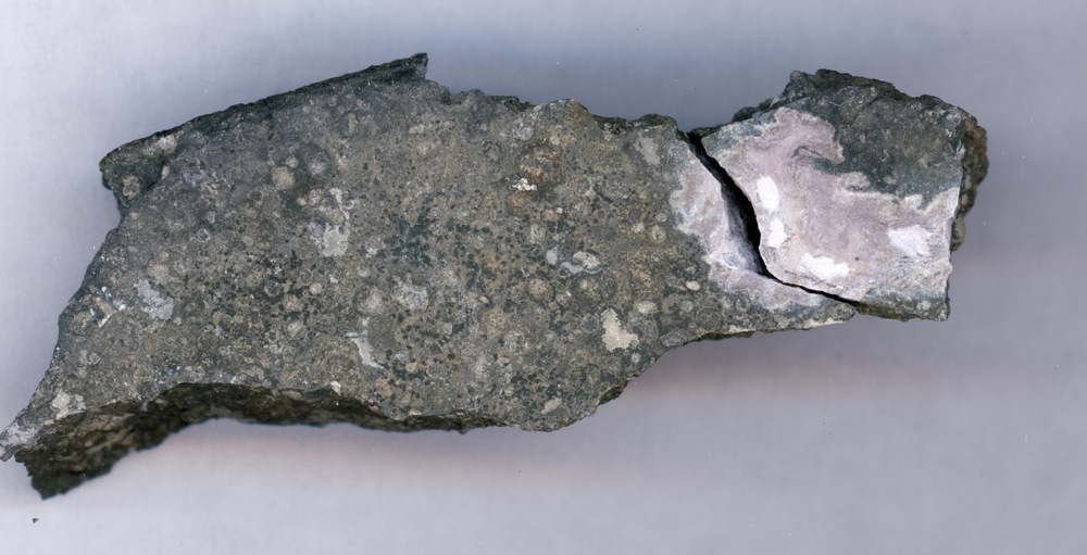 This close-up picture shows a ceramic-like refractory inclusion (pink inclusion) still embedded into the meteorite in which it was found. Refractory inclusions are the oldest-known rocks in the solar system (4.5 billion years old). Analysis of the uranium isotope ratios of such inclusions demonstrates that a long-lived isotope of the radioactive element curium was present in the solar system when this inclusion was formed. The inclusion measures 1.5 centimers (.59 inches) in length. - Image Credit: Origins Lab, University of Chicago