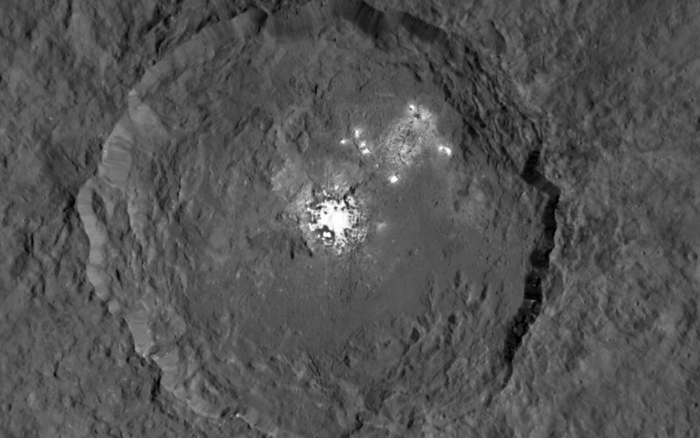 This image taken from NASA's Dawn spacecraft in orbit around the dwarf planet Ceres shows the very bright patches of material in the crater Occator and elsewhere. New observations using the HARPS spectrograph on the ESO 3.6-metre telescope at La Silla in Chile have revealed unexpected daily changes on these spots, suggesting that they change under the influence of sunlight. -   Image Credit:  NASA/JPL-Caltech/UCLA/MPS/DLR/IDA