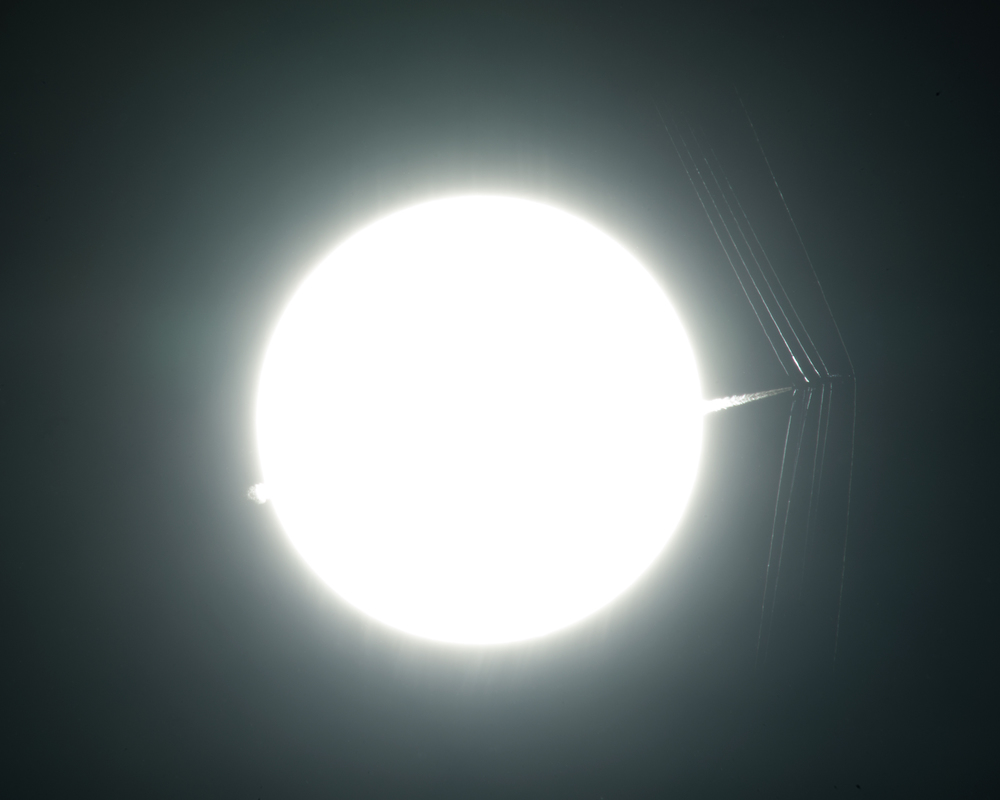 An Air Force Test Pilot School T-38 passes in front of the sun at supersonic speed, creating shockwaves that are captured using schlieren photography to visualize supersonic flow. - Image Credits: NASA Photo / Ken Ulbrich
