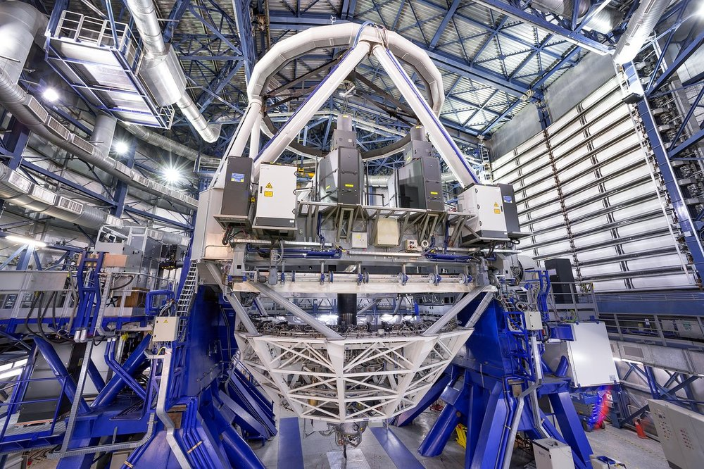 This image shows the new laser system on Unit Telescope 4 of the VLT. The black units just above the centre are the laser launch telescopes and the lasers themselves and the support electronics boxes appear to the sides of them. – Image Credit: ESO/F. Kamphues
