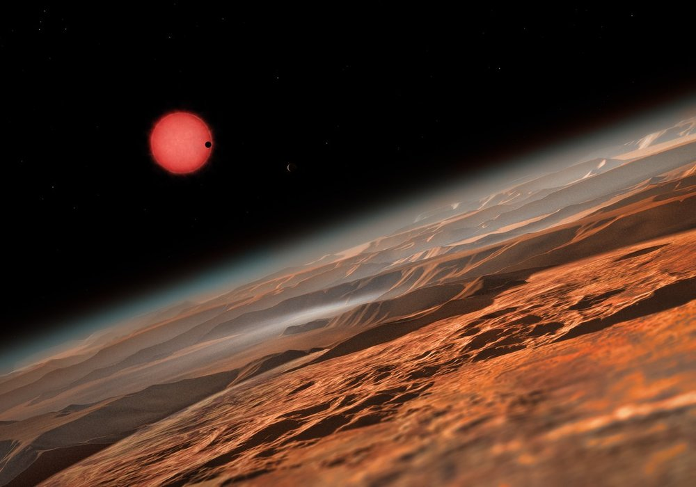 This artist's impression shows an imagined view from close to one of the three planets orbiting an ultracool dwarf star just 40 light-years from Earth that were discovered using the TRAPPIST telescope at ESO's La Silla Observatory. These worlds have sizes and temperatures similar to those of Venus and Earth and are the best targets found so far for the search for life outside the Solar System. They are the first planets ever discovered around such a tiny and dim star.   In this view one of the inner planets is seen in transit across the disc of its tiny and dim parent star. Image Credit: ESO/M. Kornmesser